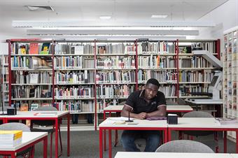 The picture shows the university library. A student is reading and working in it.