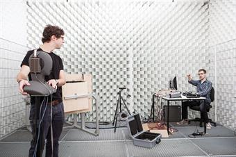 The picture shows two male students in a silent room [anechoic chamber] of the faculty of media.