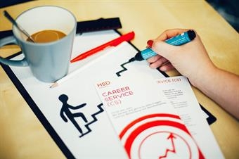A filled coffe mug, set on a writing pad. Next to it two red and White leaflets of the career Service. A Hand is drawing with a black felt pen a stickman, who is climbing some steps.