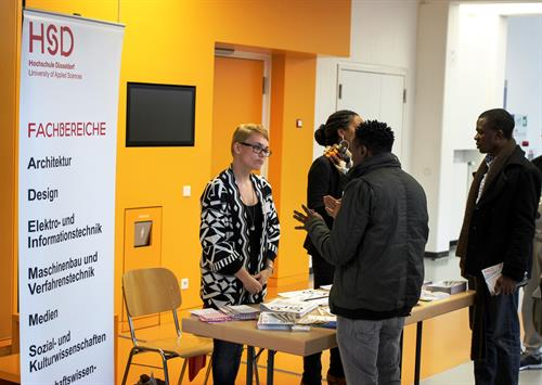 Information booth with Roll-Up and brochures is set up in front of a yellow wall. 2 International Office staff members are advising 2 dark-skinned refugees.