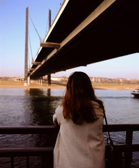 a young woman with a bright coat and brown hair is standing at a banister and watching over a big river. A dark bridge is obove her.