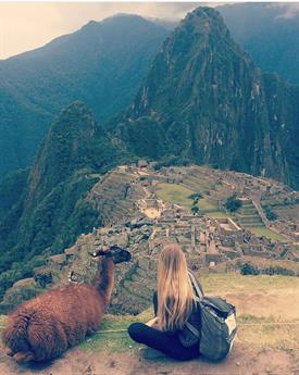 View onto the green mountains of Machu Pichu in the foreground a young blonde girl with a backpack is sitting cross-legged enjoying the view. Next to her an alpaca is lying - as well enjoying the view.