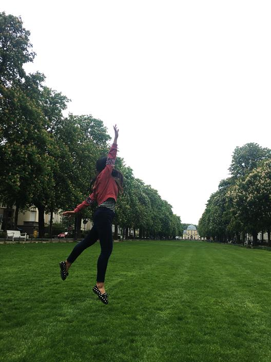 "Ran Zhao's photo ""Flying"" shows a young woman leaping up in front of the Poppelsdorfer Schloss in Bonn."