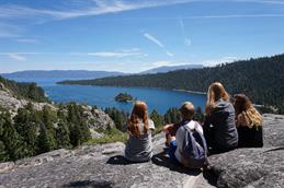 5 Young peopla are sitting on a huge rock and are watching a big lake lying below them.