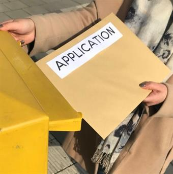A Person dressed in a nude-coloured coat, is putting a big envelope into a yellow Mailbox. The envelope has the word application written on it in big letters.