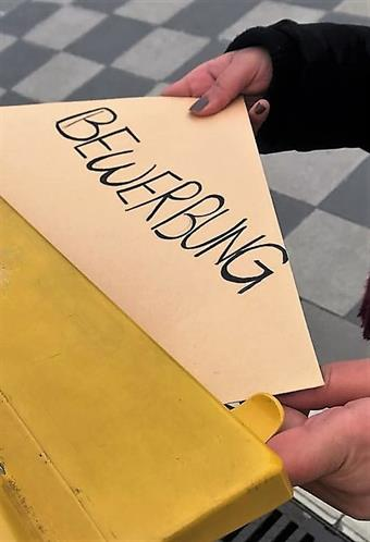 "Someone is putting a big envelope with the word ""Bewerbung"" written on it, into a yellow Mailbox."