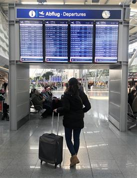 At the Airport. A big blue Screen is listing all departure flights. A Young woman with dark hair, a dark jacket and a small suitcase is standing in front of the screen is looking up.