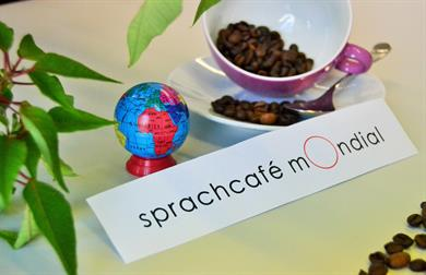 A smal colourful globe next to a pink cup, which is filled with coffee beans. Below it, the writing: Sprachcafé mOndial.
