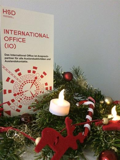 A red-and white leaflet with the Internationale Office logo next to a twig of pine decorated with red Christmas ornaments an candles