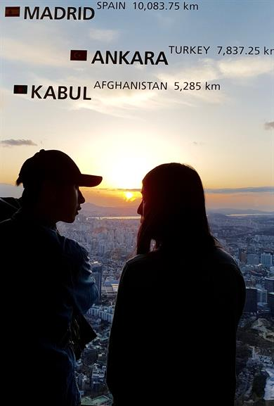 The picture shows a woman and a man, apparently a young couple, watching the sunset from the Namsan Tower in Seoul.